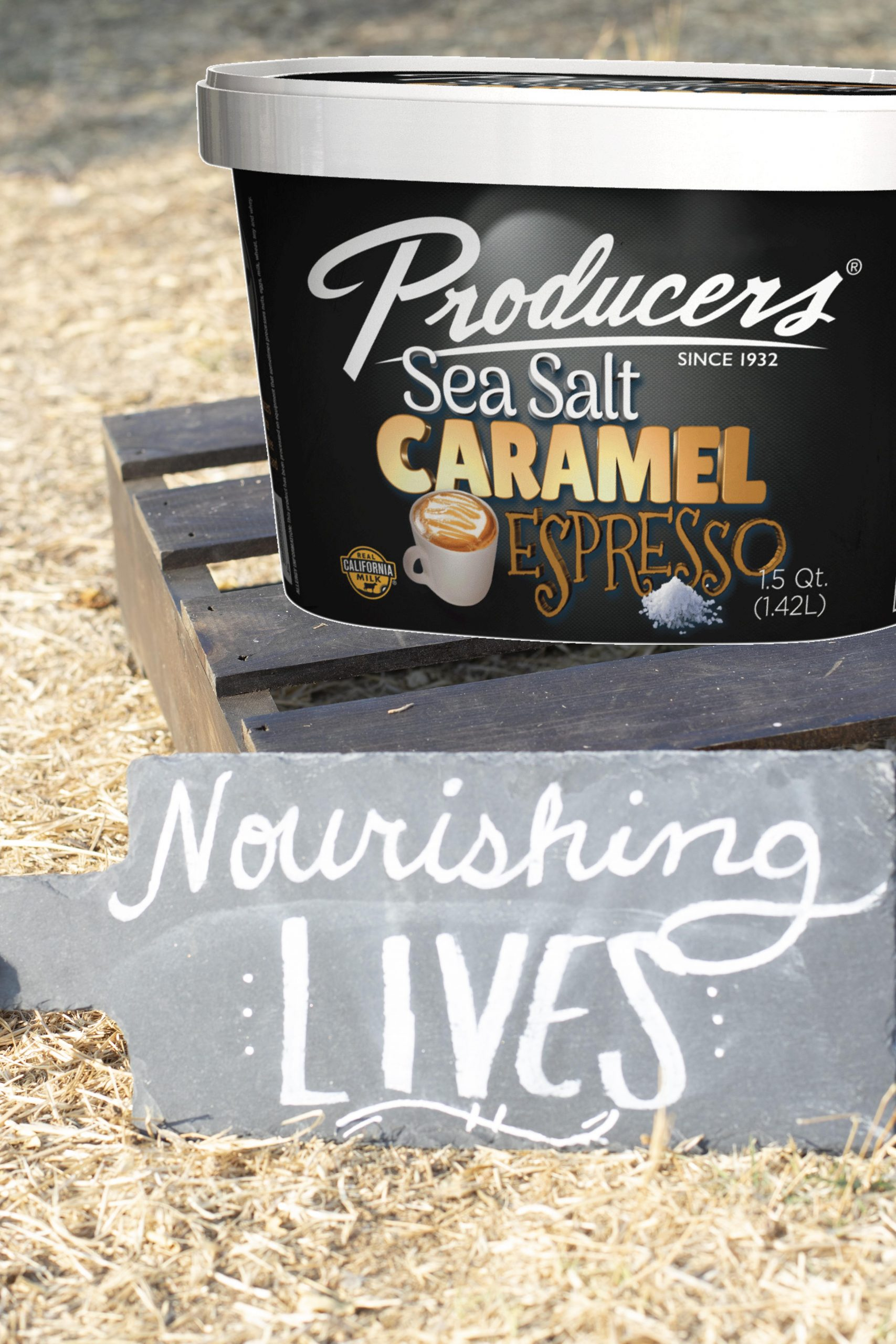 Sea Salt Caramel Espresso Producers Ice Cream sitting on wood in the middle of a hay field.