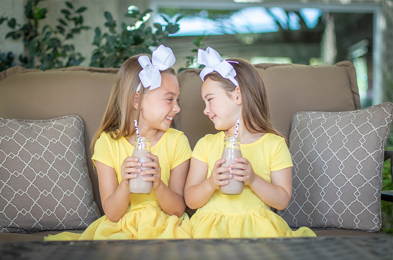 Two little girls drinking Old Fashioned Chocolate Milk with straws.