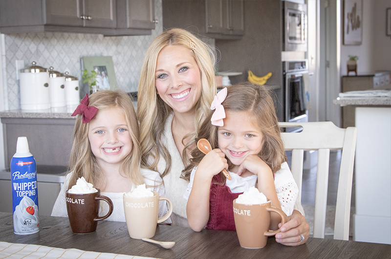 Producers Influencer with her two daughters drinking hot chocolate with Producers Whipped topping on top.