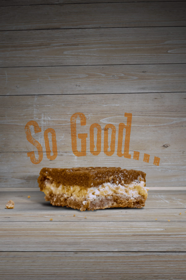 "Pumpkin Cheesecake Bar with a wood backdrop behind it. Words on the wall say, ""So Good..."""
