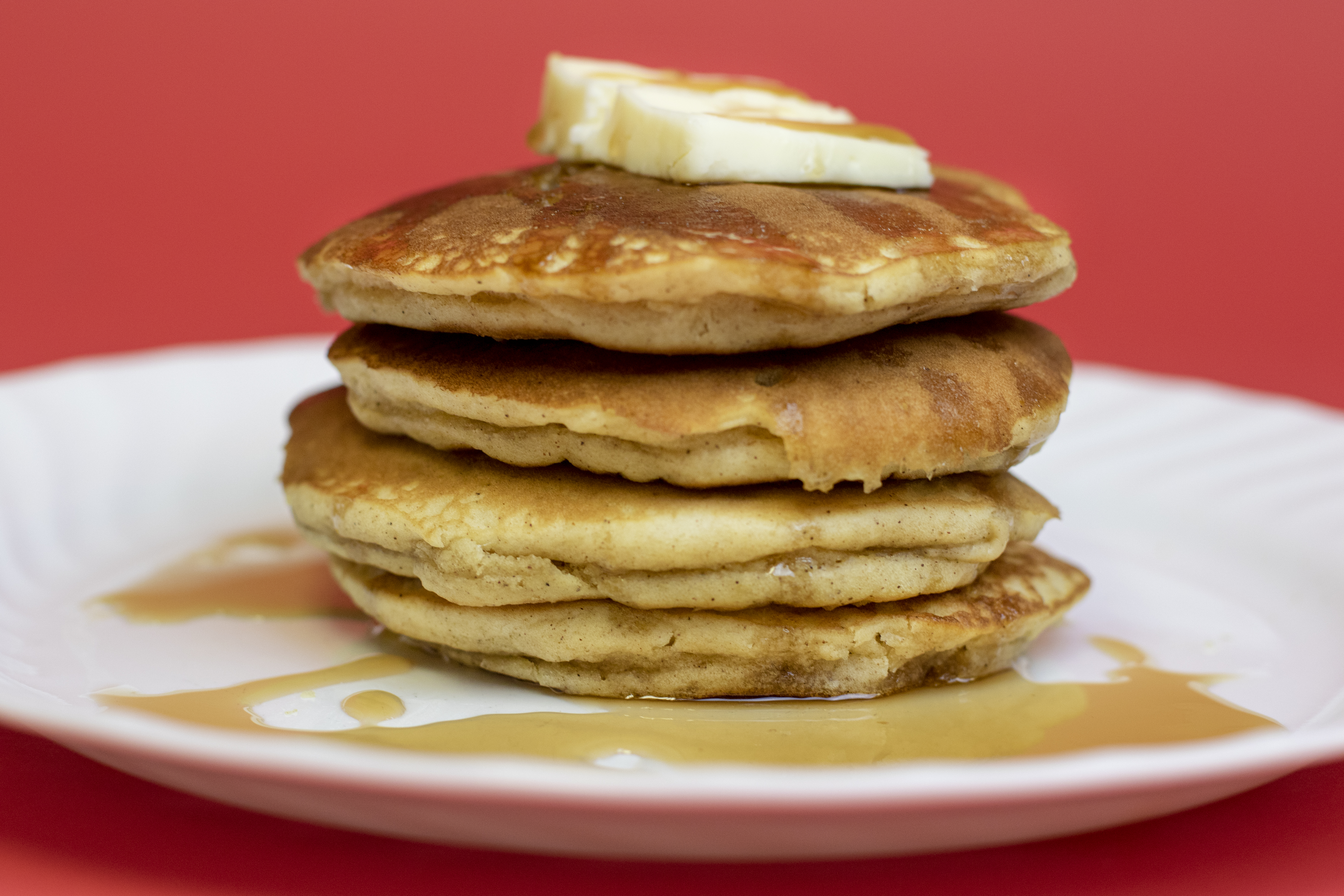 Apple cinnamon pancakes with butter and syrup drizzling over the sides on a white plate with a red backdrop