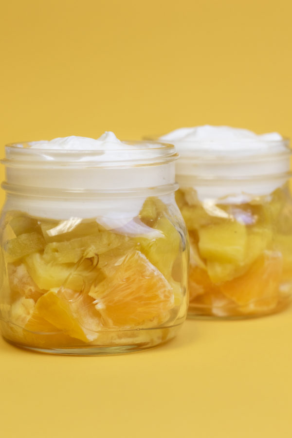Oranges, pineapple, and whipped topping in a clear mason jar to look like a candy cane on a yellow backdrop.