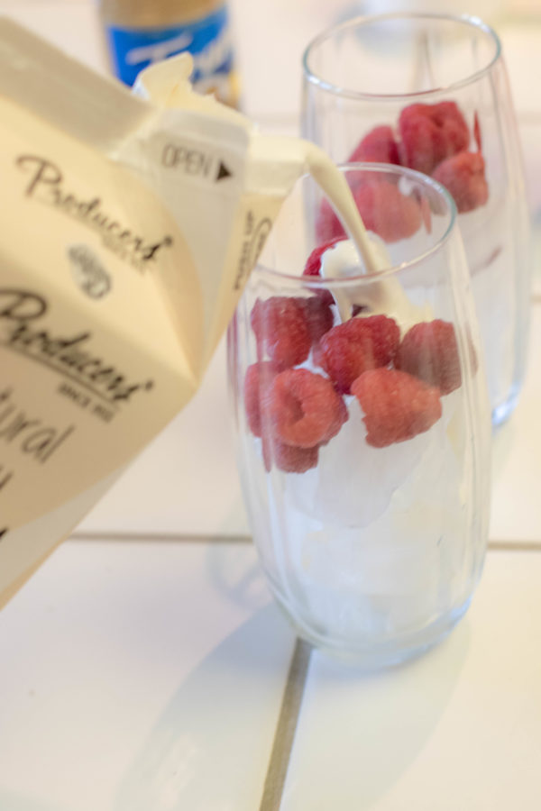 Natural Cream being poured into a clear glass with ice and raspberries on a kitchen counter.
