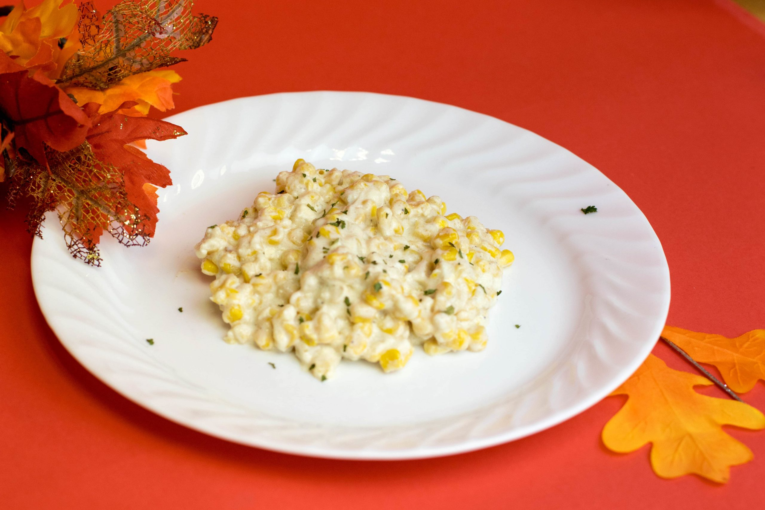 Creamed corn on a white plate laying on a flat red background surrounded by fall leaves.