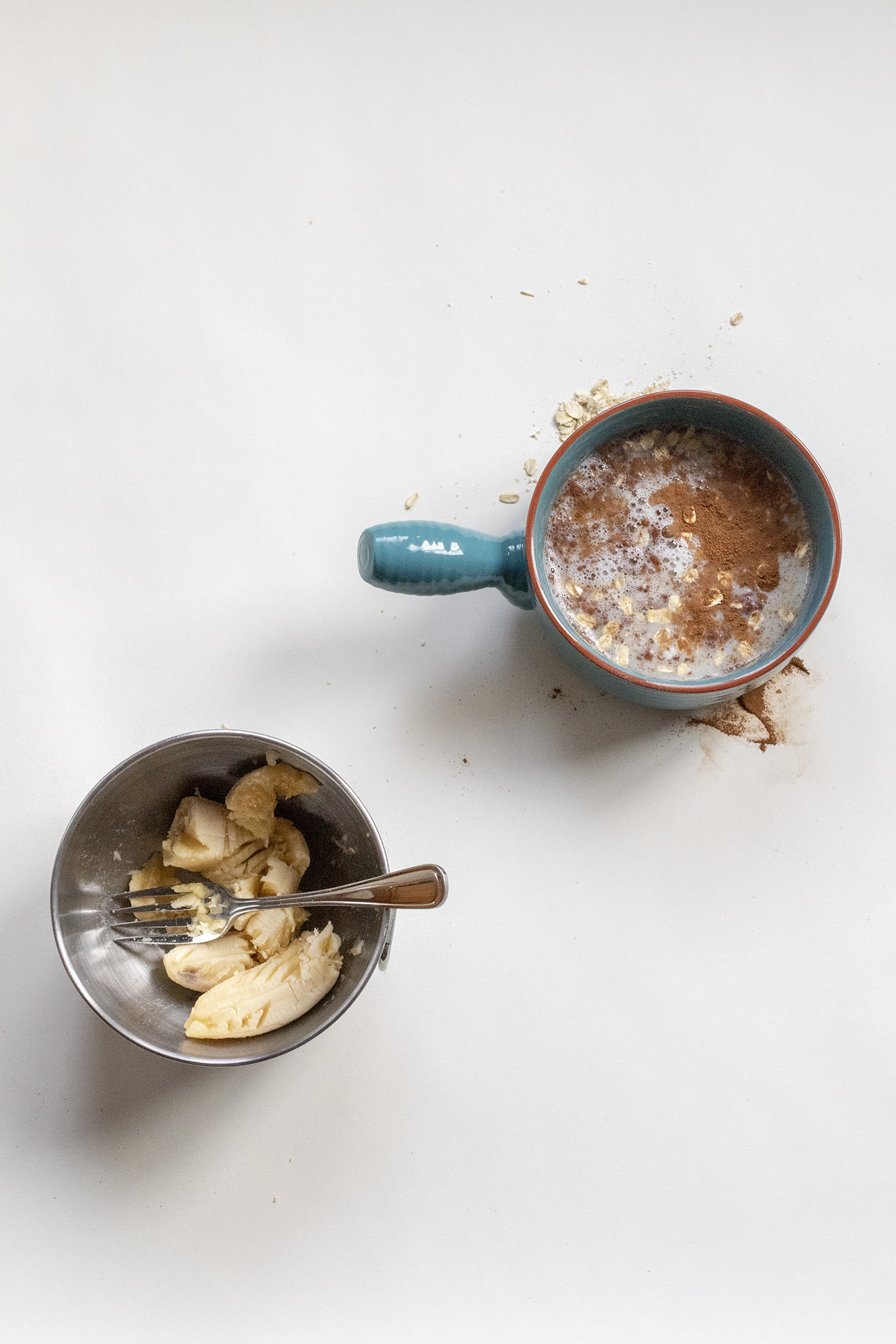 Mashed band with a fork in a metal bowl and egg whites with cinnamon and milk in another blue bowl. Both on a white background.