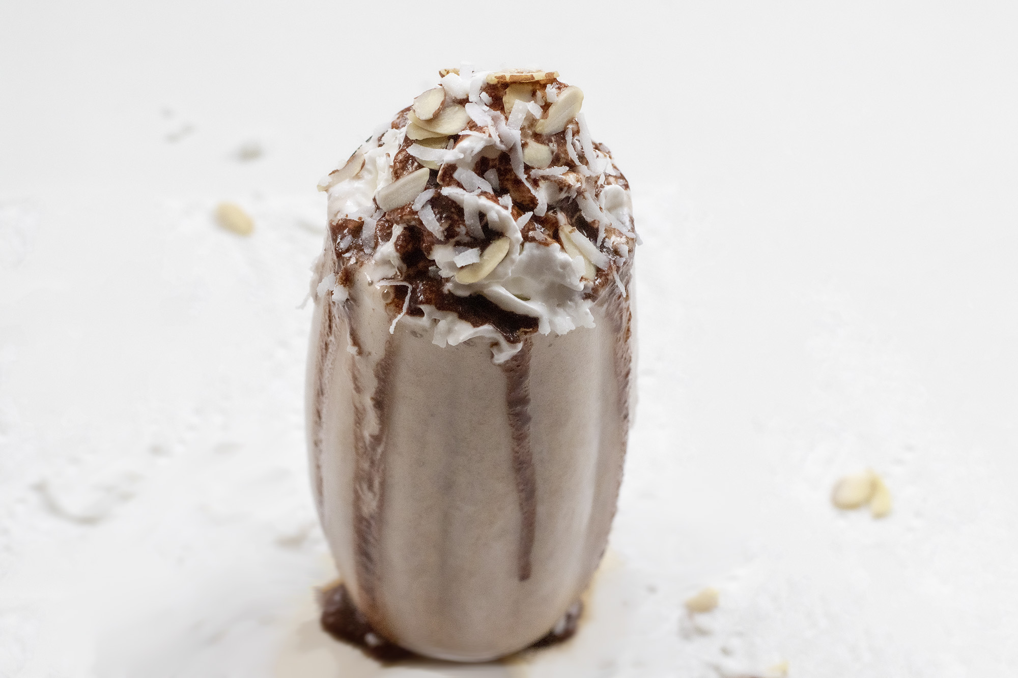Chocolate Milkshake with whipped topping, sliced almonds, and shredded coconut on a white background.