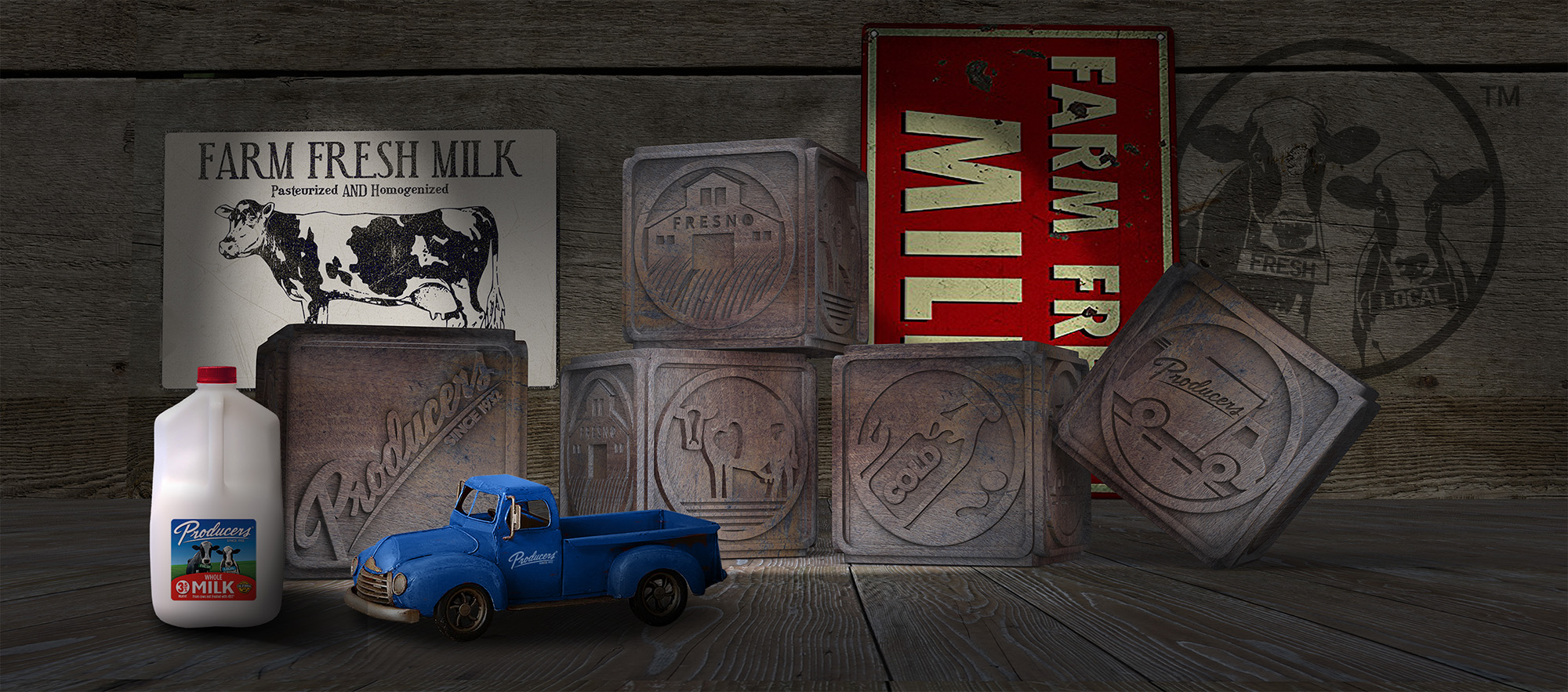 Building blocks with Producers logo on one, dairy cow on another, cold bottle of milk on another, Fresno Barn on another, and a vdelivery truck on the last one. A gallon of Producers white whole milk. Farm Fresh Signage. A blue vintage truck.