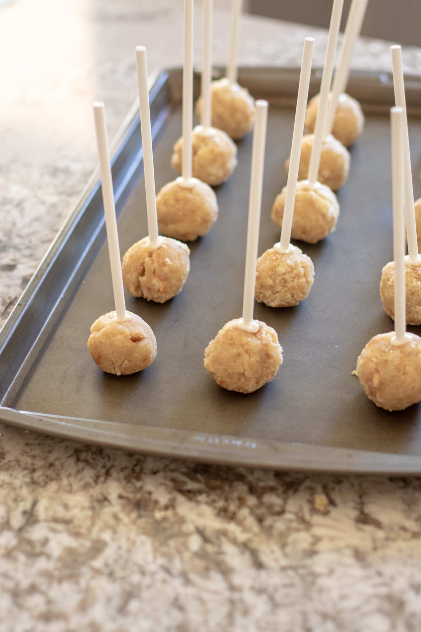 Cake rolled into balls on popsicle sticks sitting on a cookie sheet.